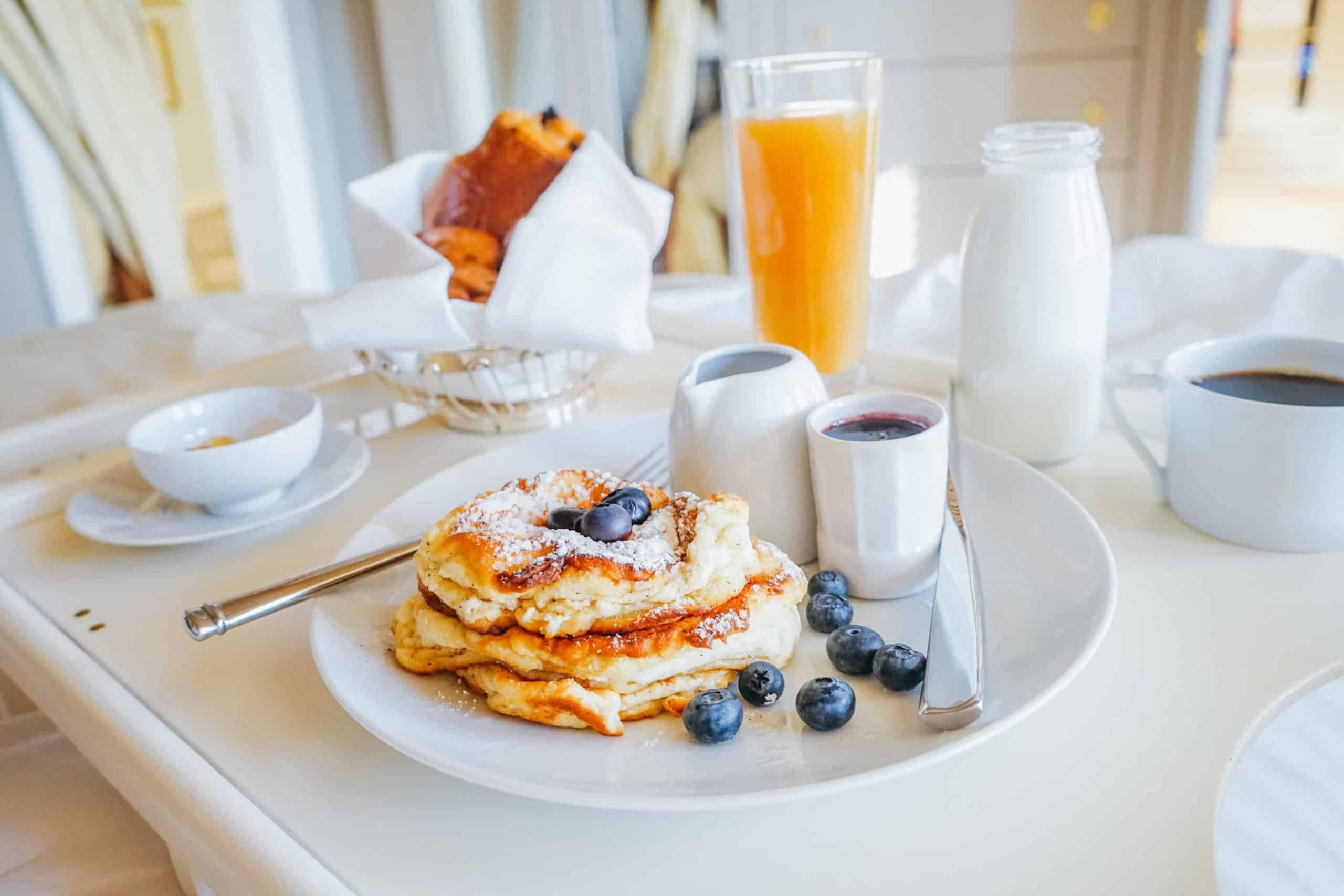 Closeup of blue berry pancakes upon a room service tray inside a guest room of The Ivy Baltimore. Orange Juice, bread rolls and a glass carafe of milk rest on the tray as well.