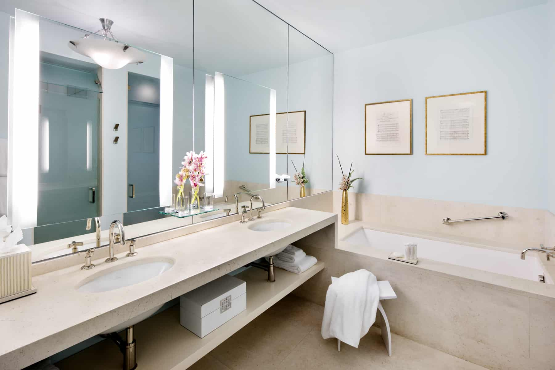 Wide Shot of the bathroom inside Suite Two of the Ivy Baltimore. By the bathtub, a towel is laid over a simple footstool.