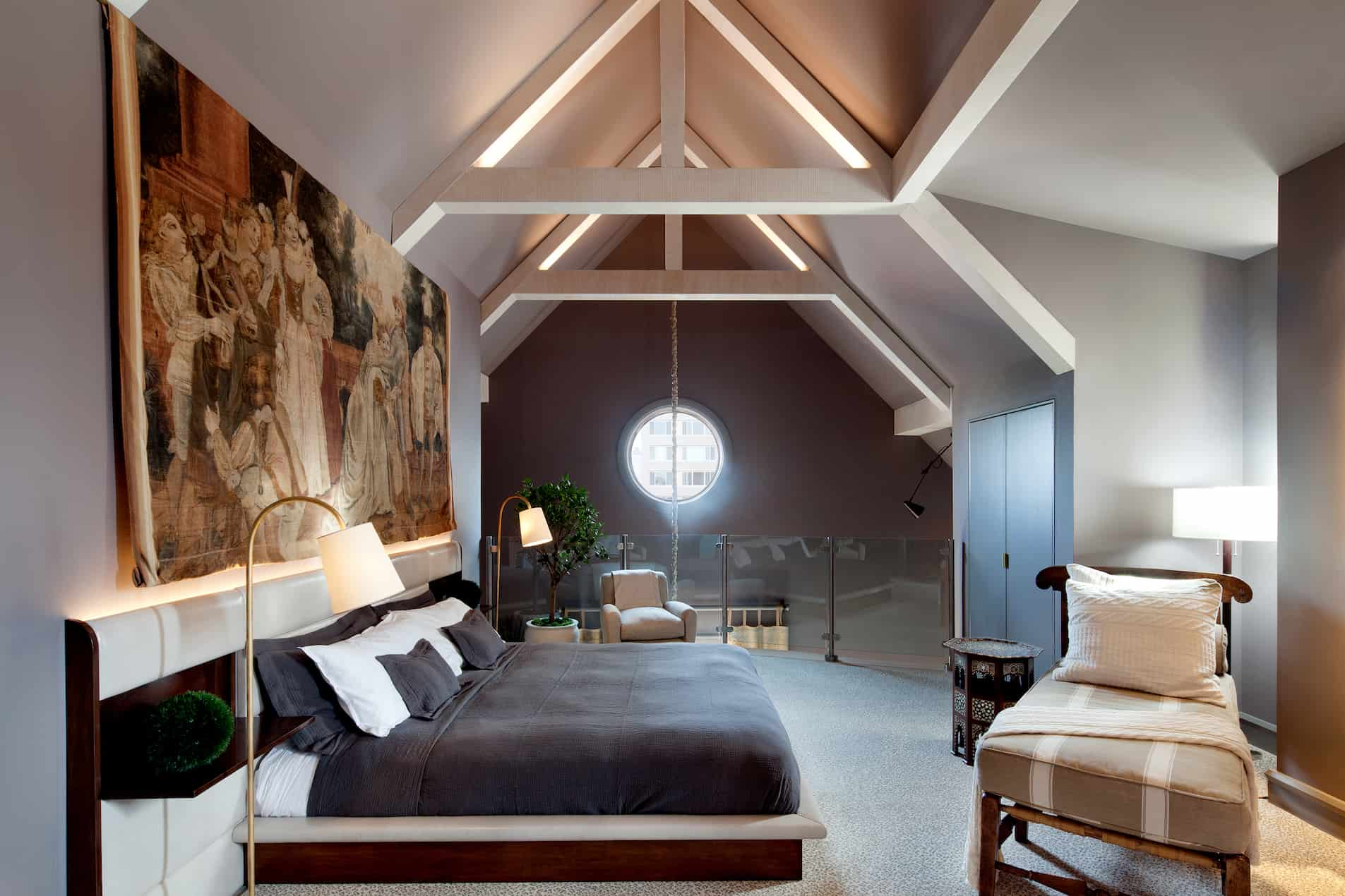Looking into the loft area of Suite Eighteen. The Ivy Balitmore's most luxurious suite offers a large bed, with detailed tapestry above. A low back lounge is placed nearby.