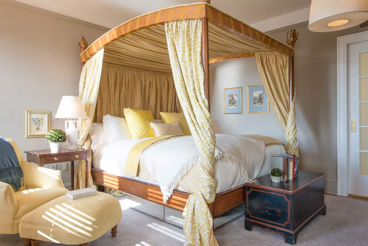 Bedroom of Suite Fourteen, inside the Ivy Hotel Baltimore. Sunlight is cast on this top side accomodation, giving extra vibrance to the gold hues of the four poster bed.
