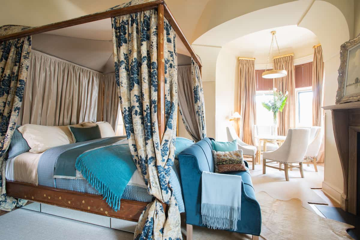 Perspective shot of Room Thirteen, dressed in blue and teal with a floral print to the four poster bed draping. This Mansion Room is situated on the corner of the building, bathing the turret side of this room in light.