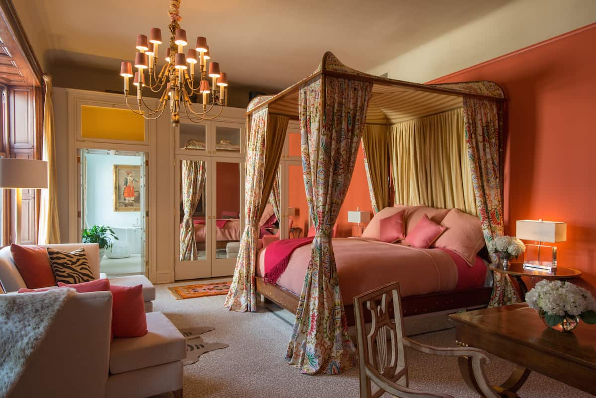 Bedroom of Suite Seven in the Ivy Hotel Baltimore. The four poster king sized bed is placed between two nightshades. This part of the mansion gives a well lit window view, with panel mirrors on the door just beyond.