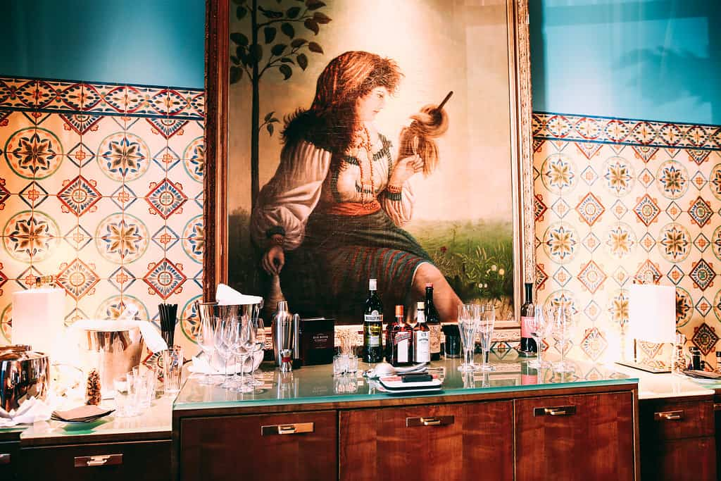 Set up at the Mansion Bar. Beneath the oil painting, a paneled cabinet holds ice buckets along with a selection of wine and cocktails.