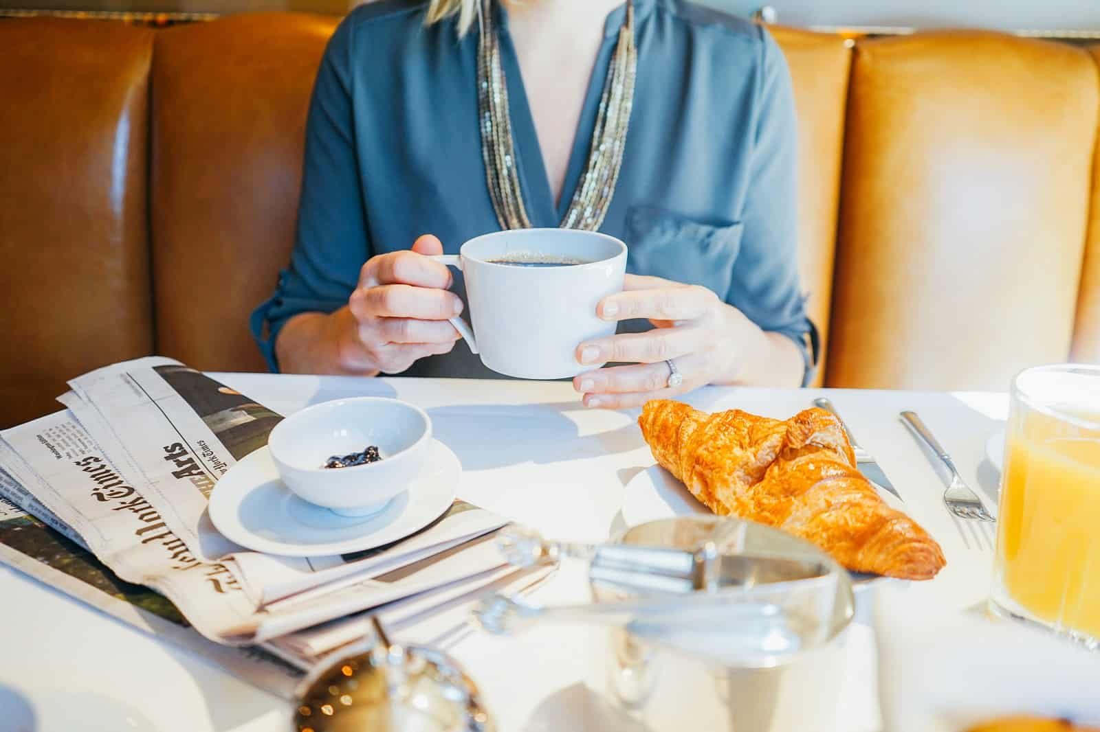 Closeup of a guest picking up a coffee cup, with a croissant on a plate in front. In this dining booth, another cup and saucer rests atop a folded newspaper.