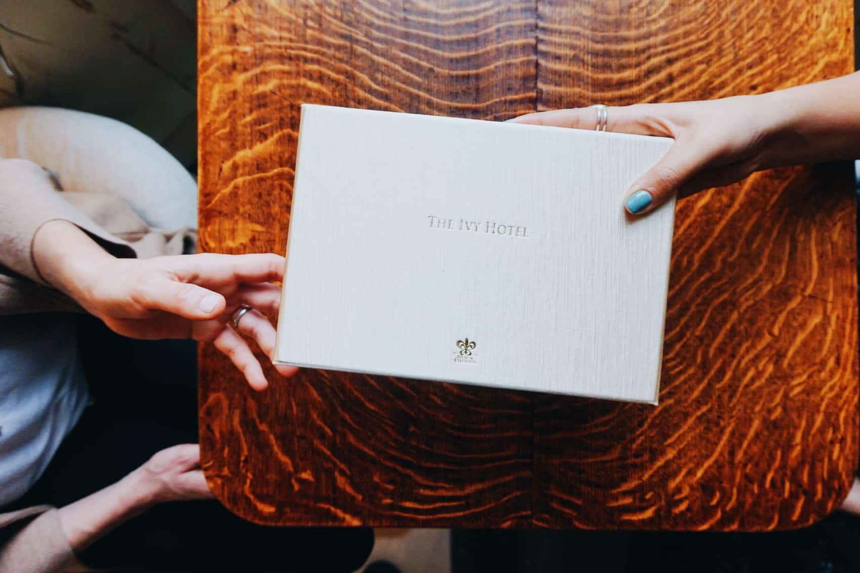 Person handing another a gift box from the Ivy Baltimore. A gift certificate is inside where the receiver can enjoy a variety of perks.