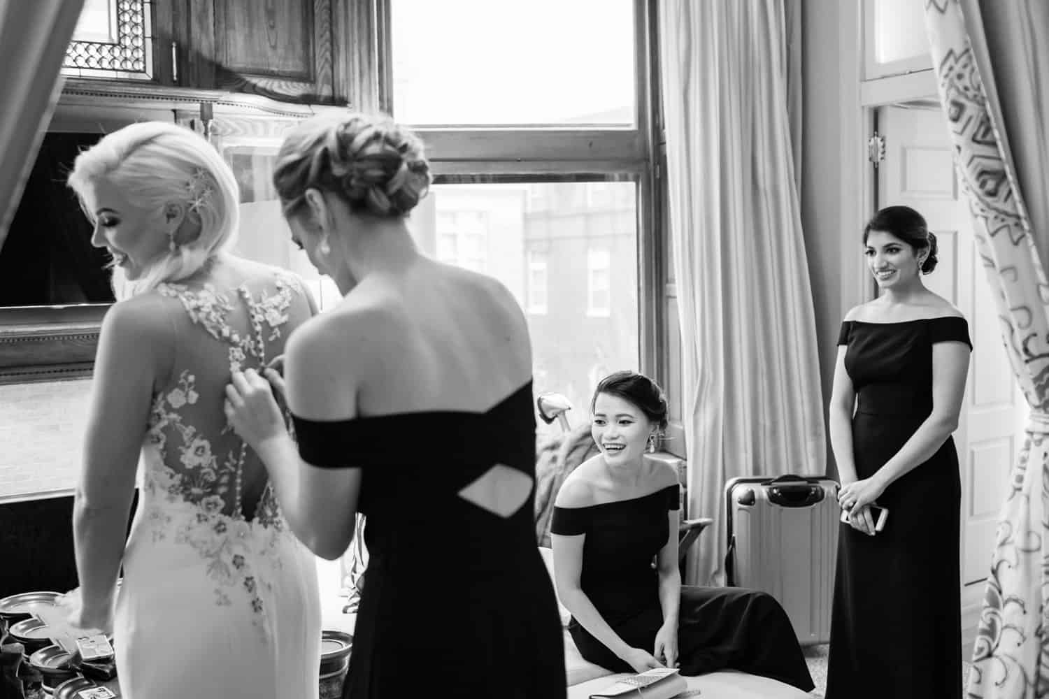 Wedding party member assisting the bride. Photo taken by Merkle Photography.