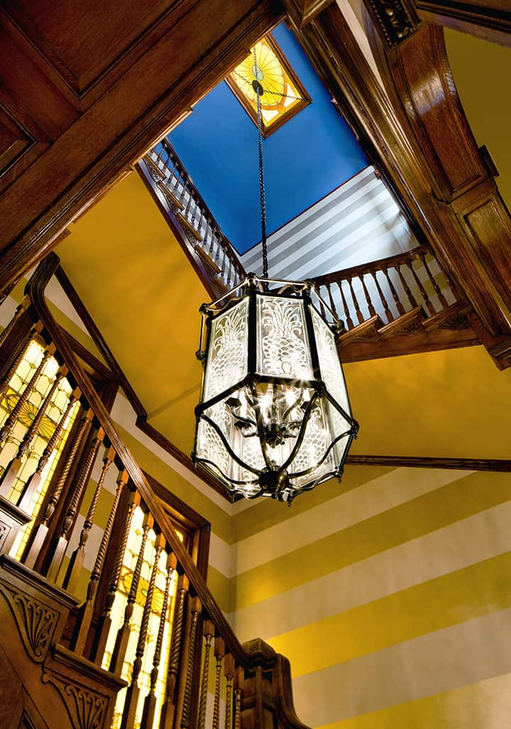 Looking into the stairwell of The Ivy Baltimore hotel. A glass chandelier lights the area, along with stained glass