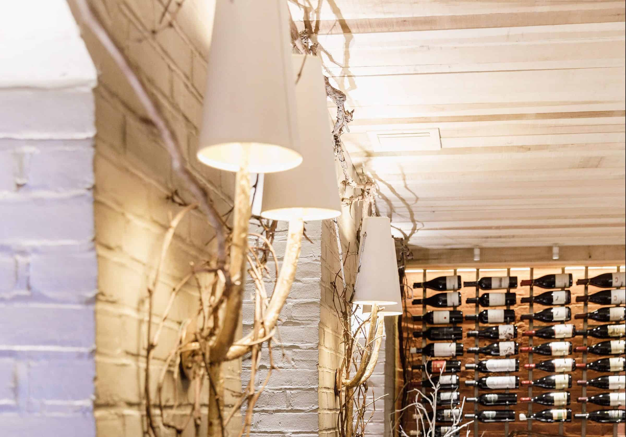 Wall sconces with rustic vines and wine racks in the Robert Parker Wine Cellar at Magdalena Restaurant.
