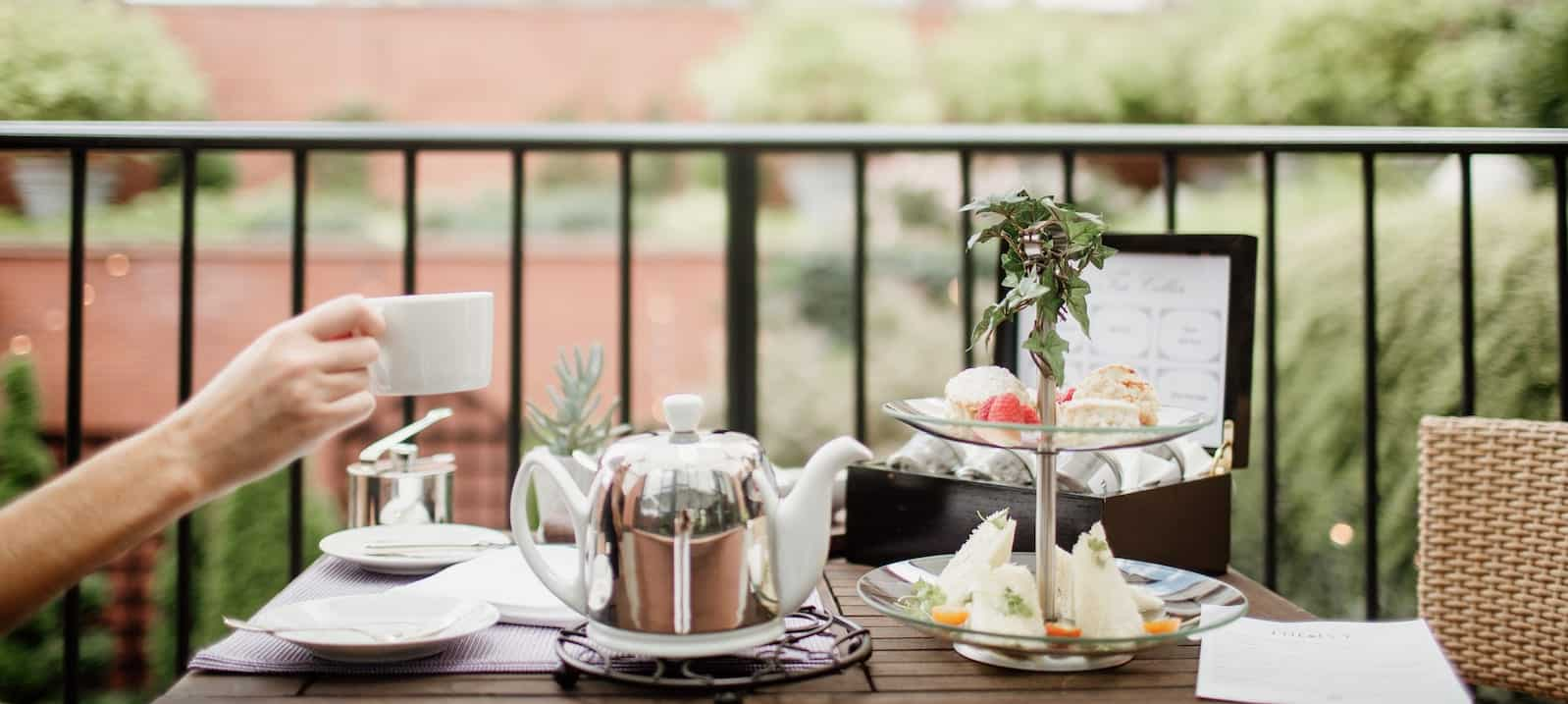 Pot of tea and sandwiches on table outside at The Ivy Hotel in Baltimore, Maryland.