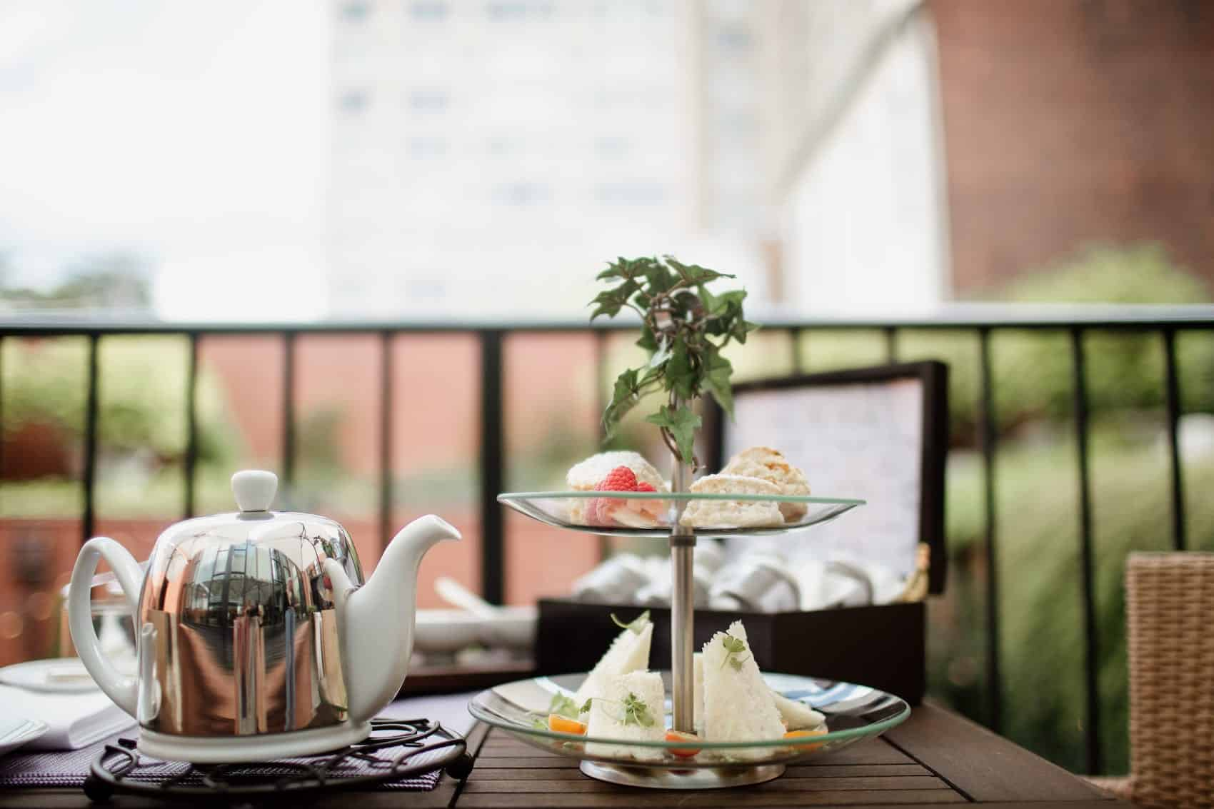Teapot next to sandwiches on the terrace at The Ivy Hotel.