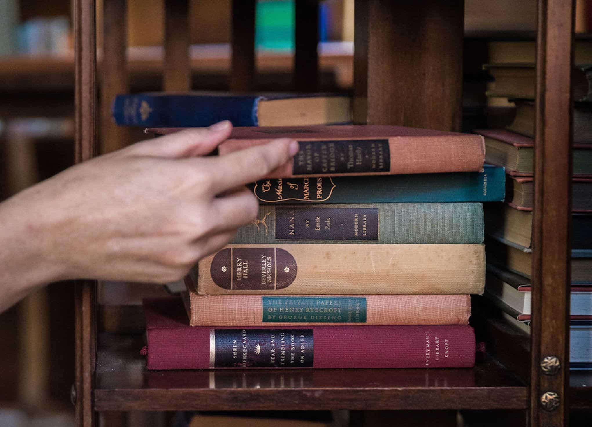 Hand grabbing stack of books.