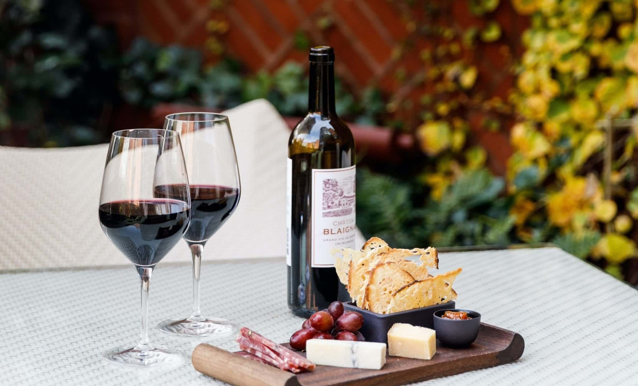 Wine and cheese on outdoor table.