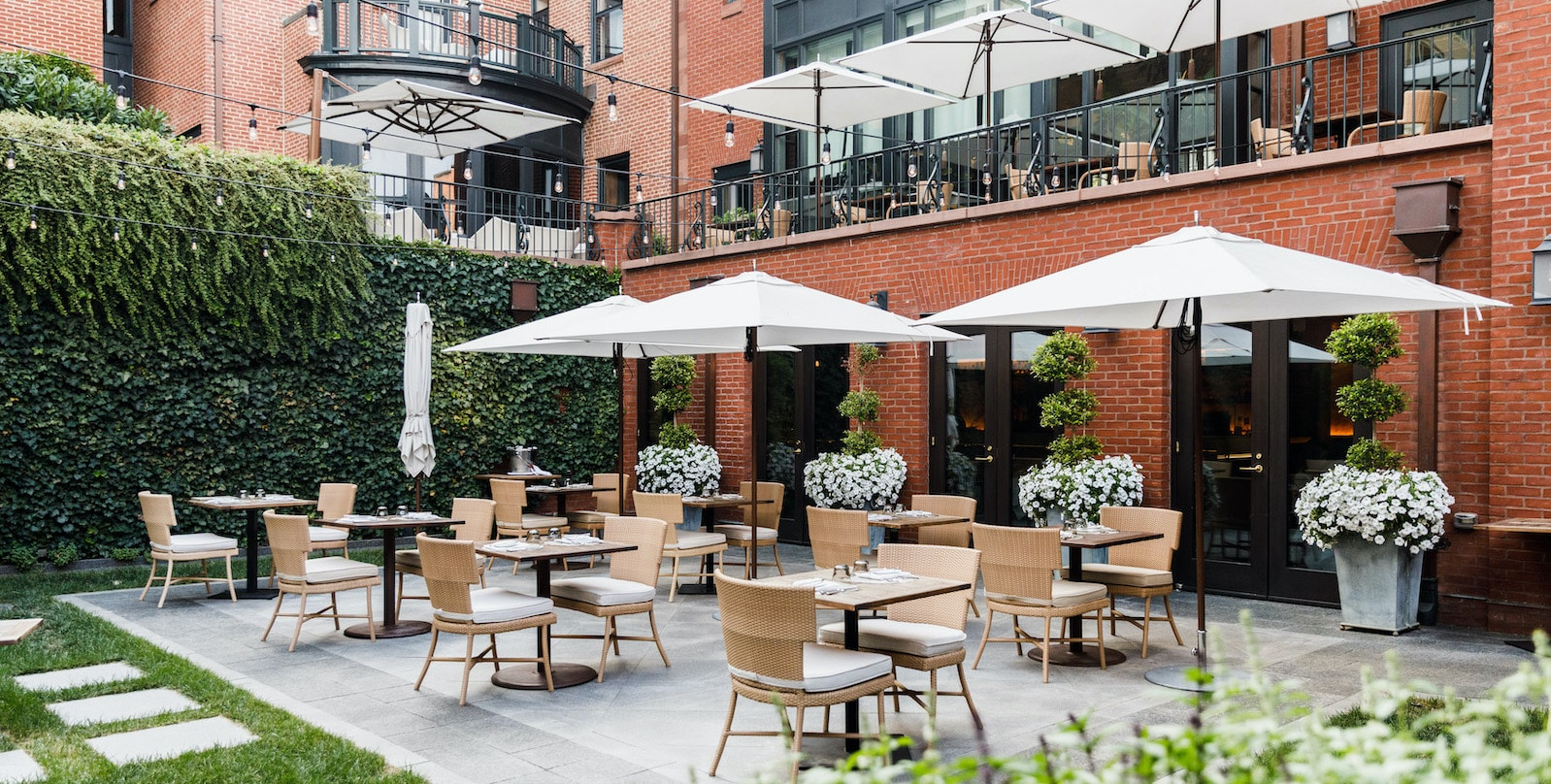 Tables, chairs and umbrellas set up in courtyard against lush ivy and brick face of the hotel.
