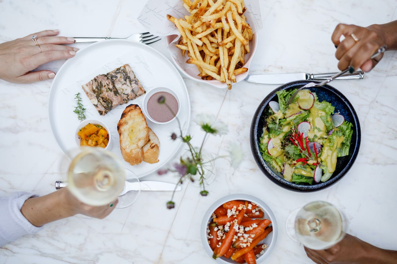 Overhead image of two guests enjoying white wine with their entrées and sides.