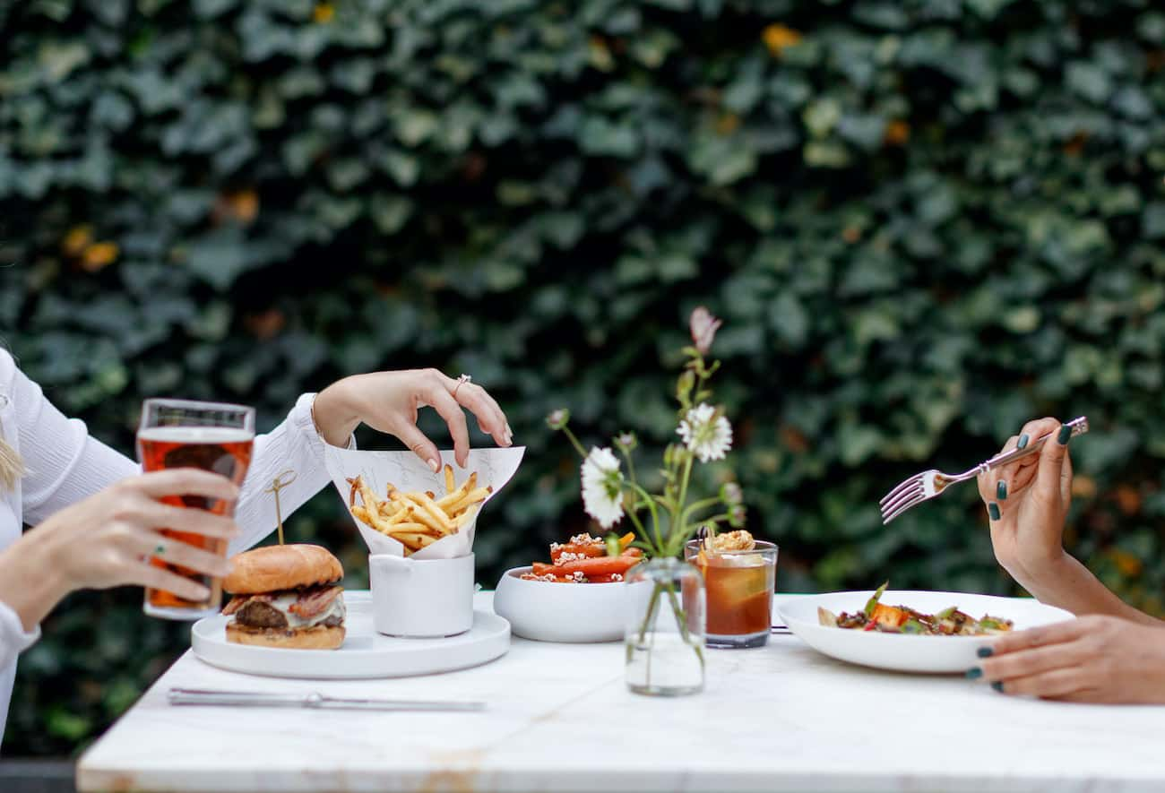 Two guests enjoy lunch in the courtyard. Guest to the left enjoys a pint of beer with gourmet burger and french fries while the guest on the right enjoys a whisky cocktail with a salad dish.