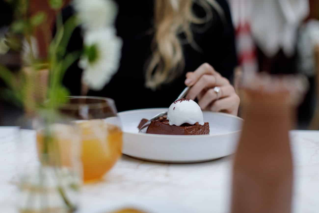 Blonde hair woman enjoys dark chocolate mousse cake with milk ice cream and orange caramel.