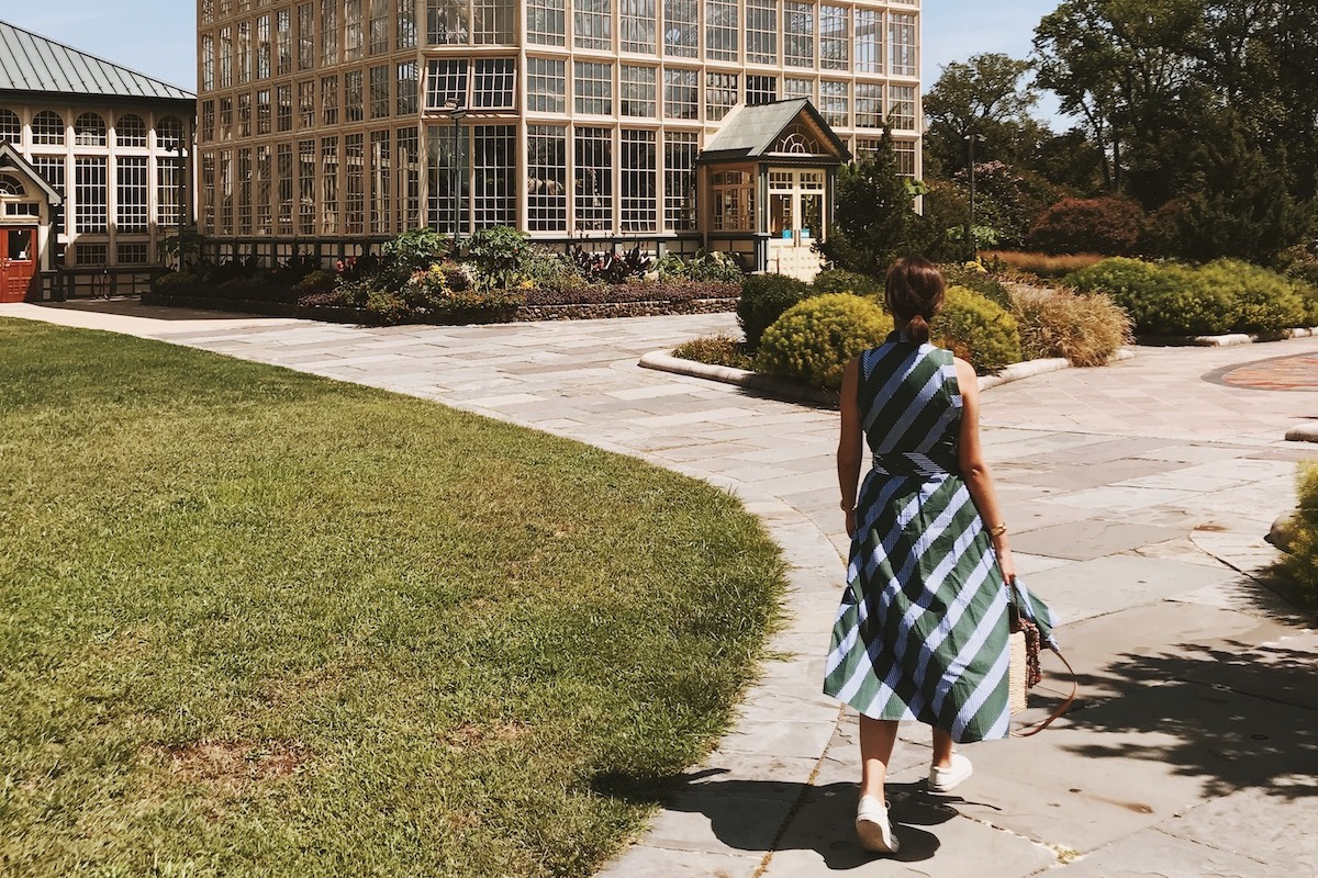 Woman in blue and green striped dress walking outside on a stone path toward a conservatory.