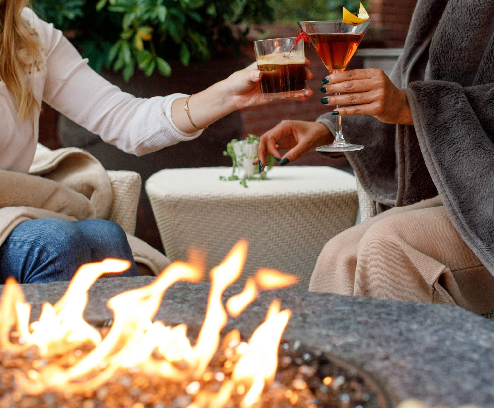 Two people cheers their drink in front of a fire