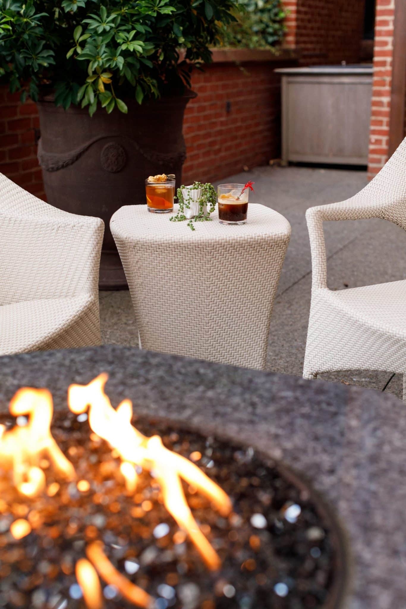 Two drinks on a table in front of a fire pit