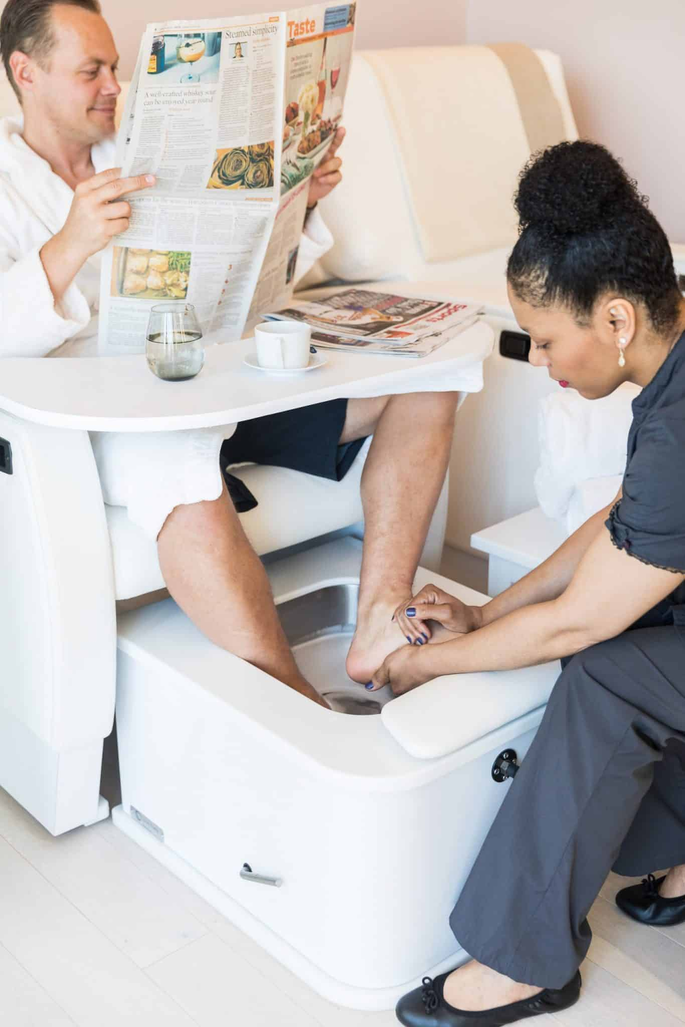 A person reading the newspaper and getting a pedicure