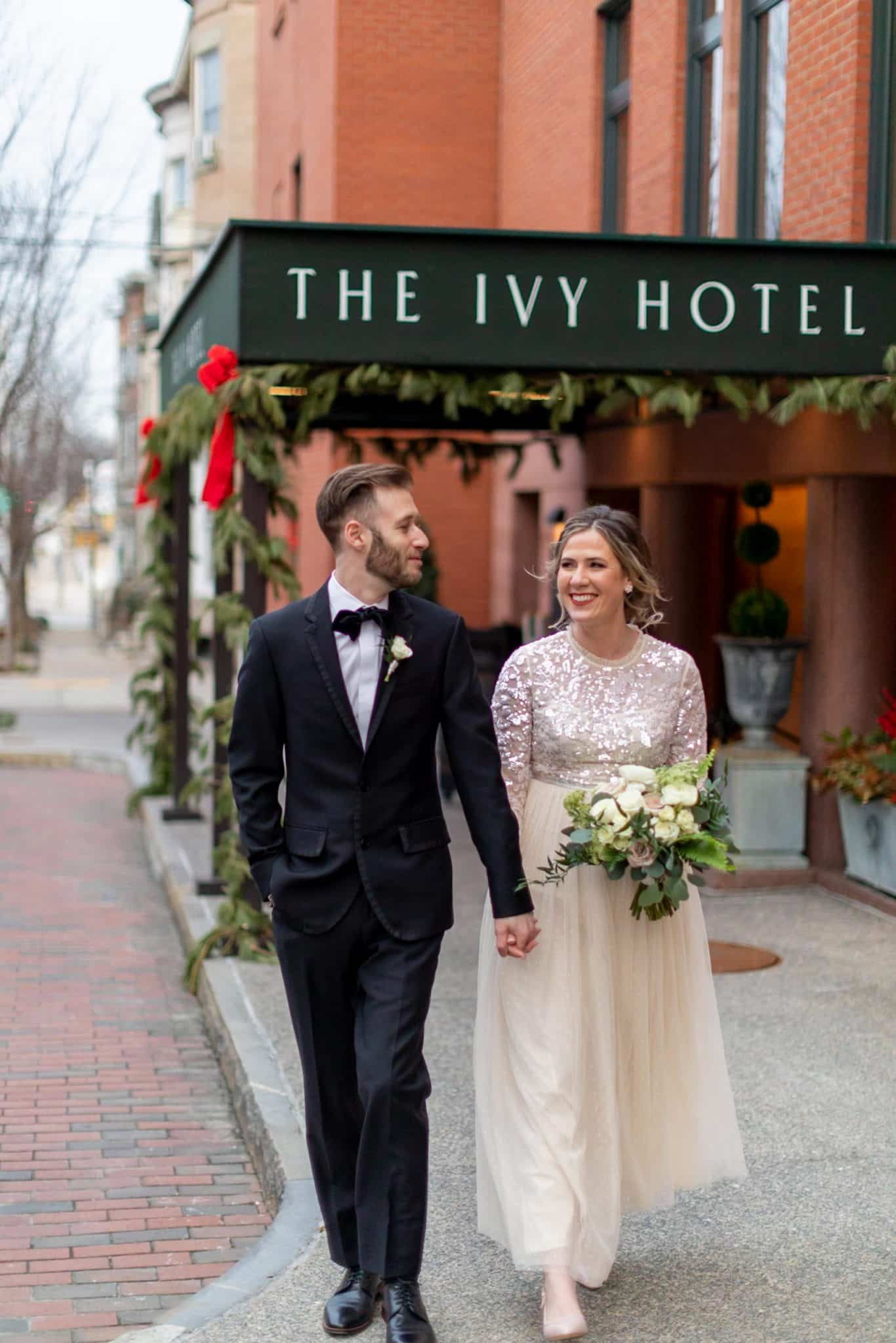 Bride and groom walking hand in hand in front of The Ivy Hotel awning