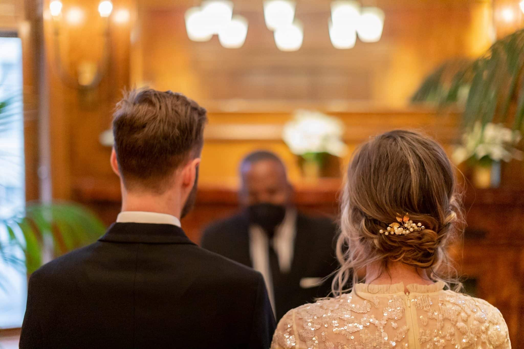 The back of the bride and groom's heads while they listen to the officiant