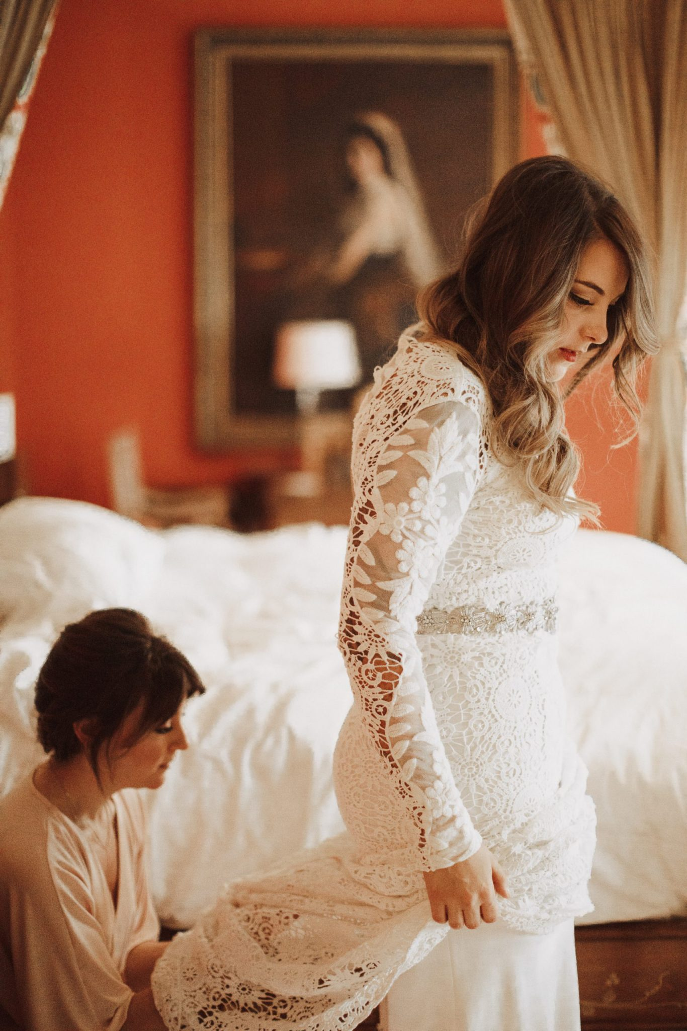 Bridesmaid assists bride with her dress train