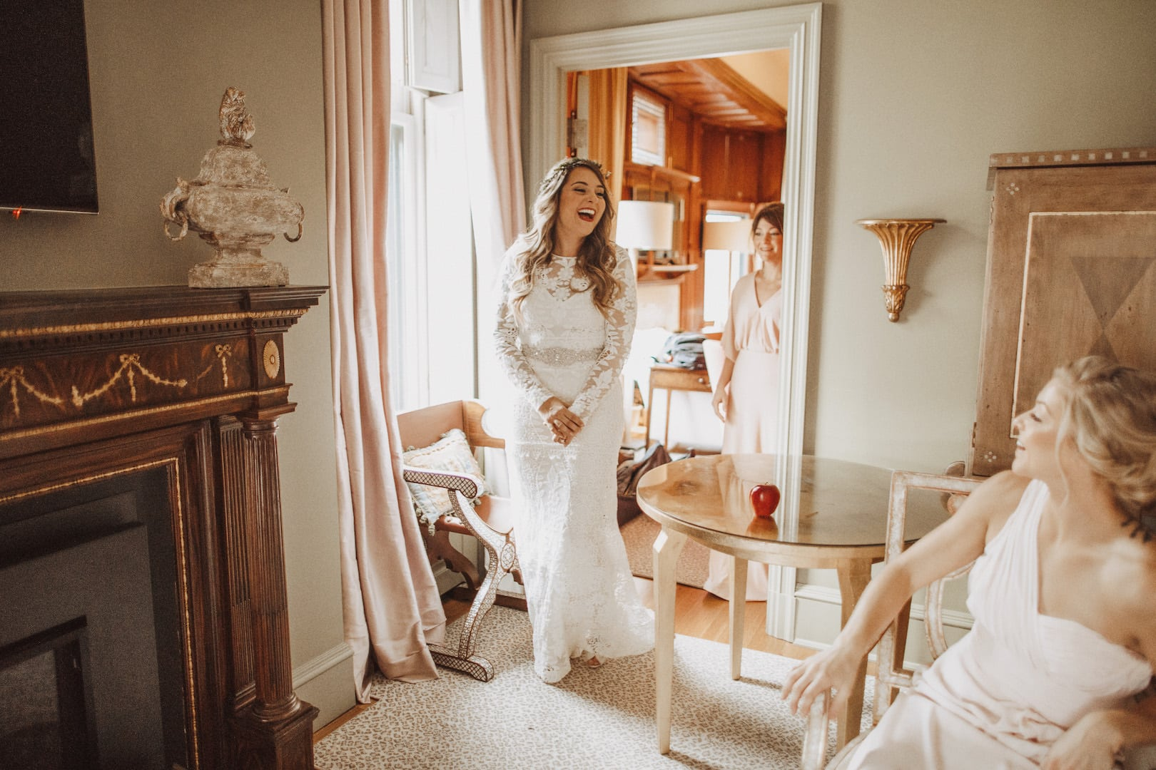 Bride laughing with bridesmaids in hotel suite