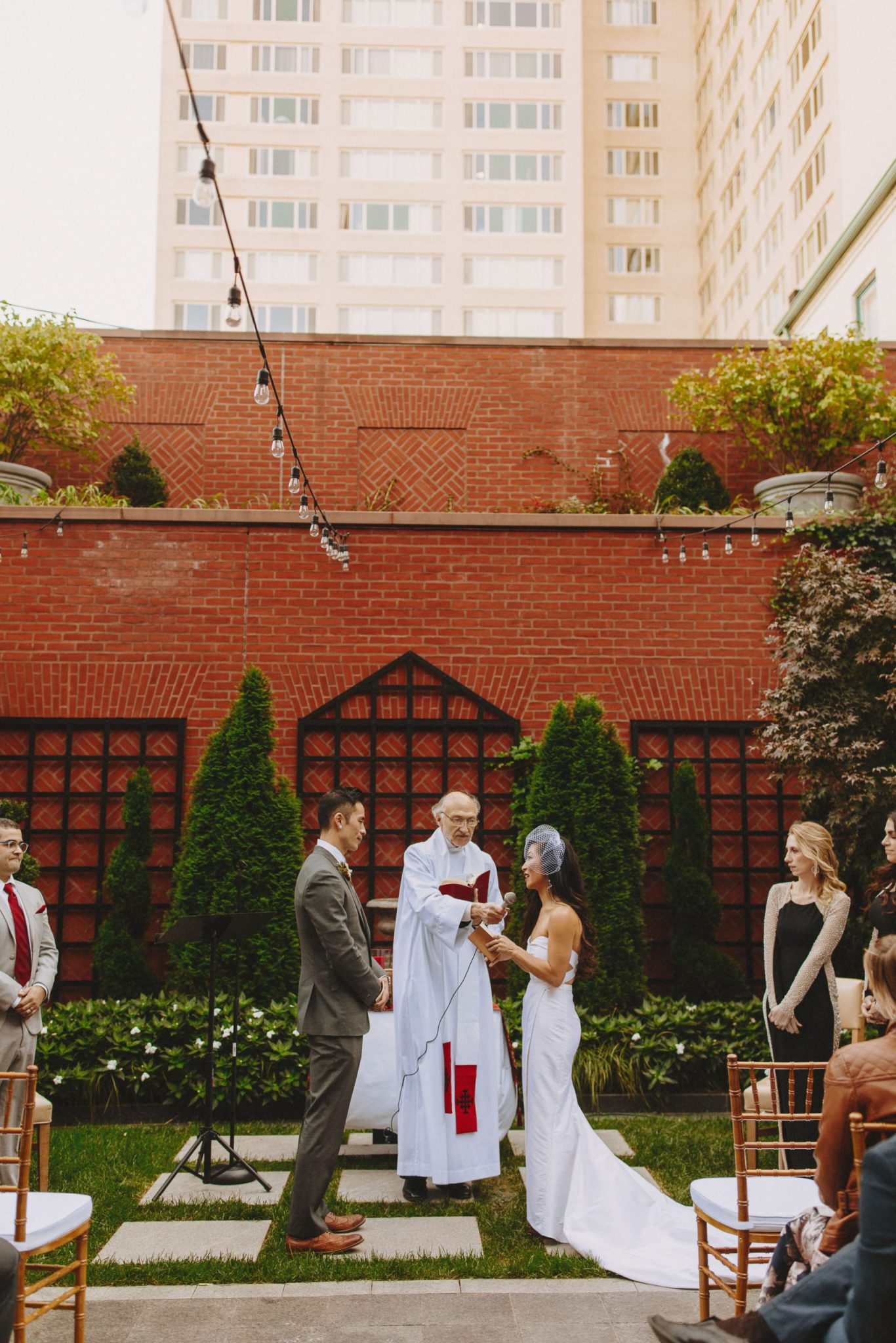 Bride and groom with the priest while reading vows