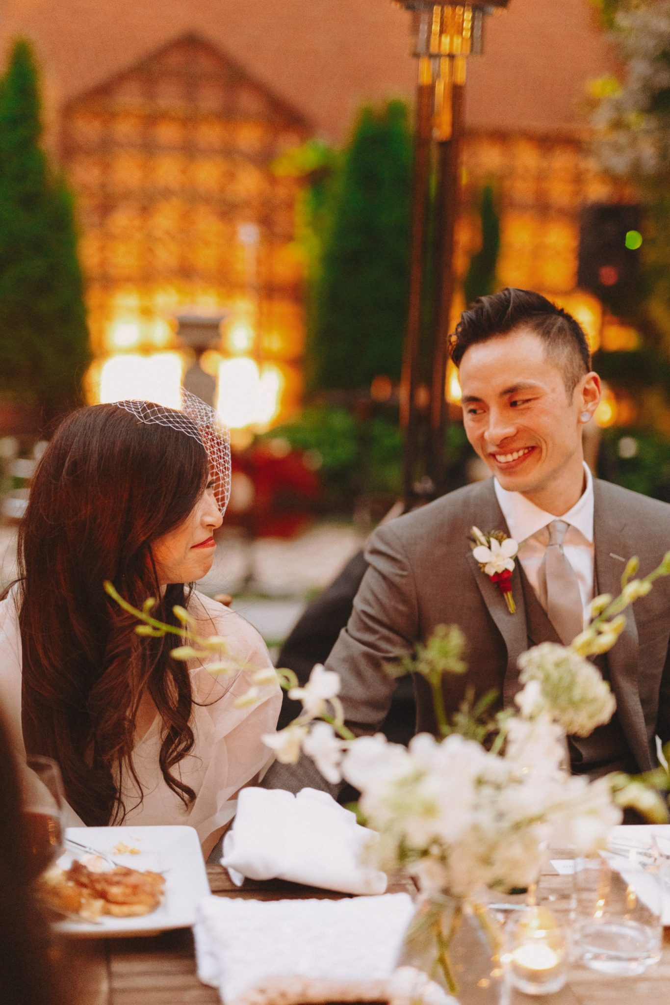 Bride and groom at the table looking at one another smiling