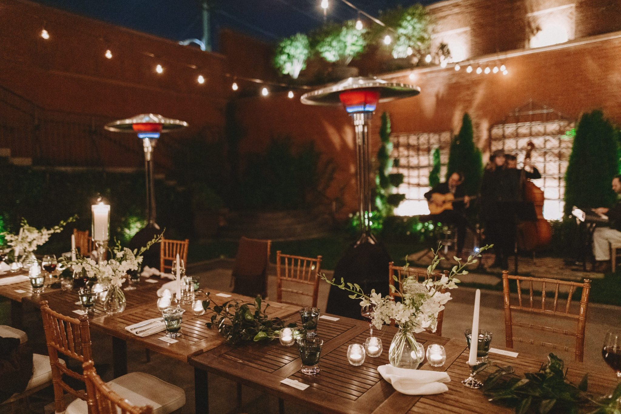 Courtyard set up for dinner with musicians in the background at night