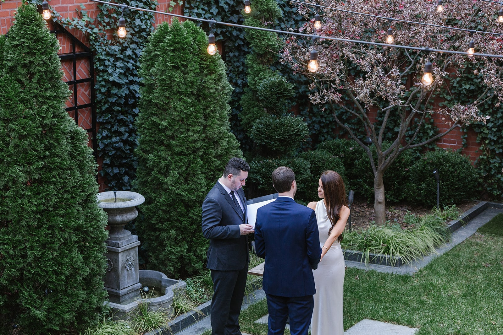 Overlook of bride, groom, and officiant in the courtyard