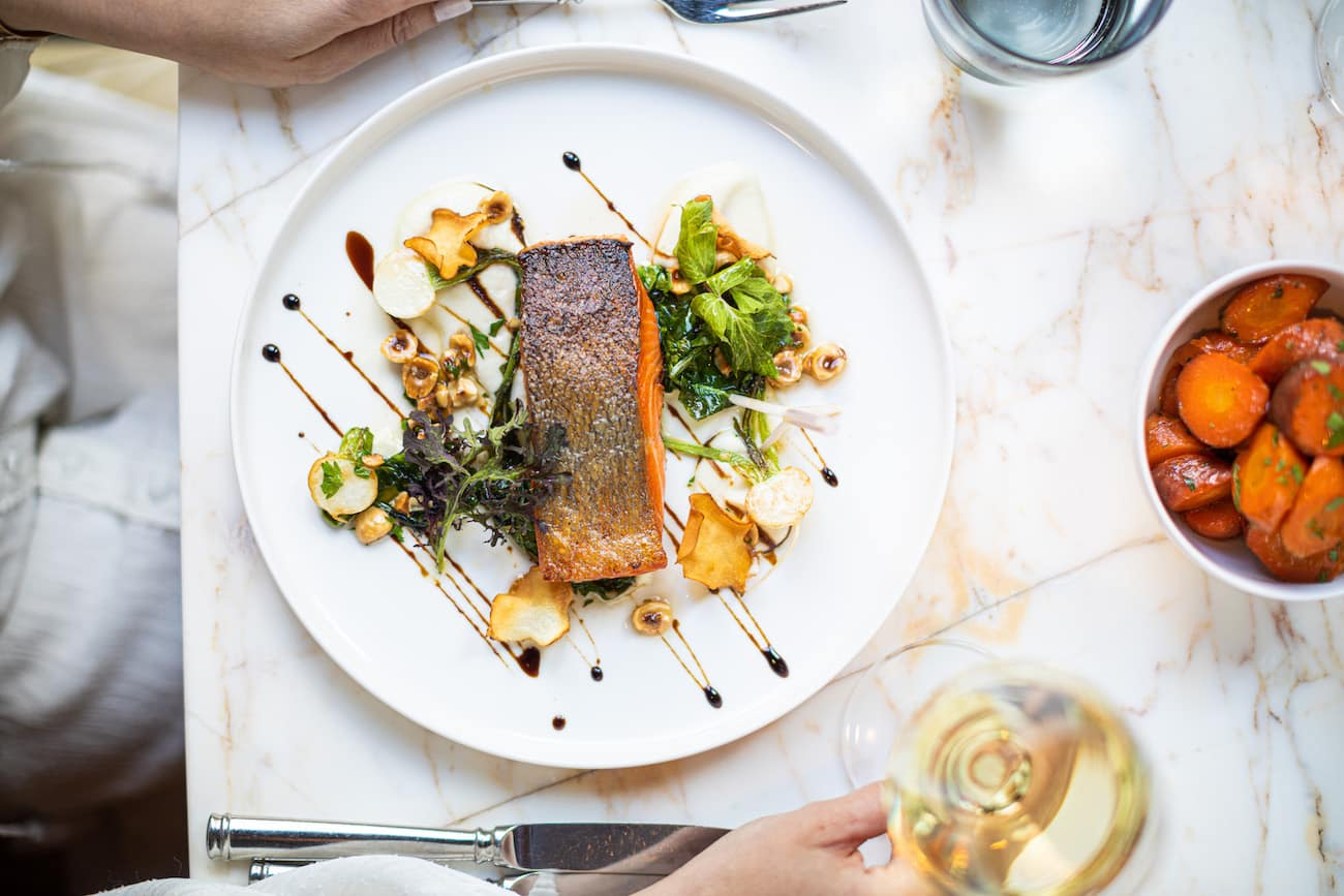 Overview of a salmon dish, white wine, and carrots